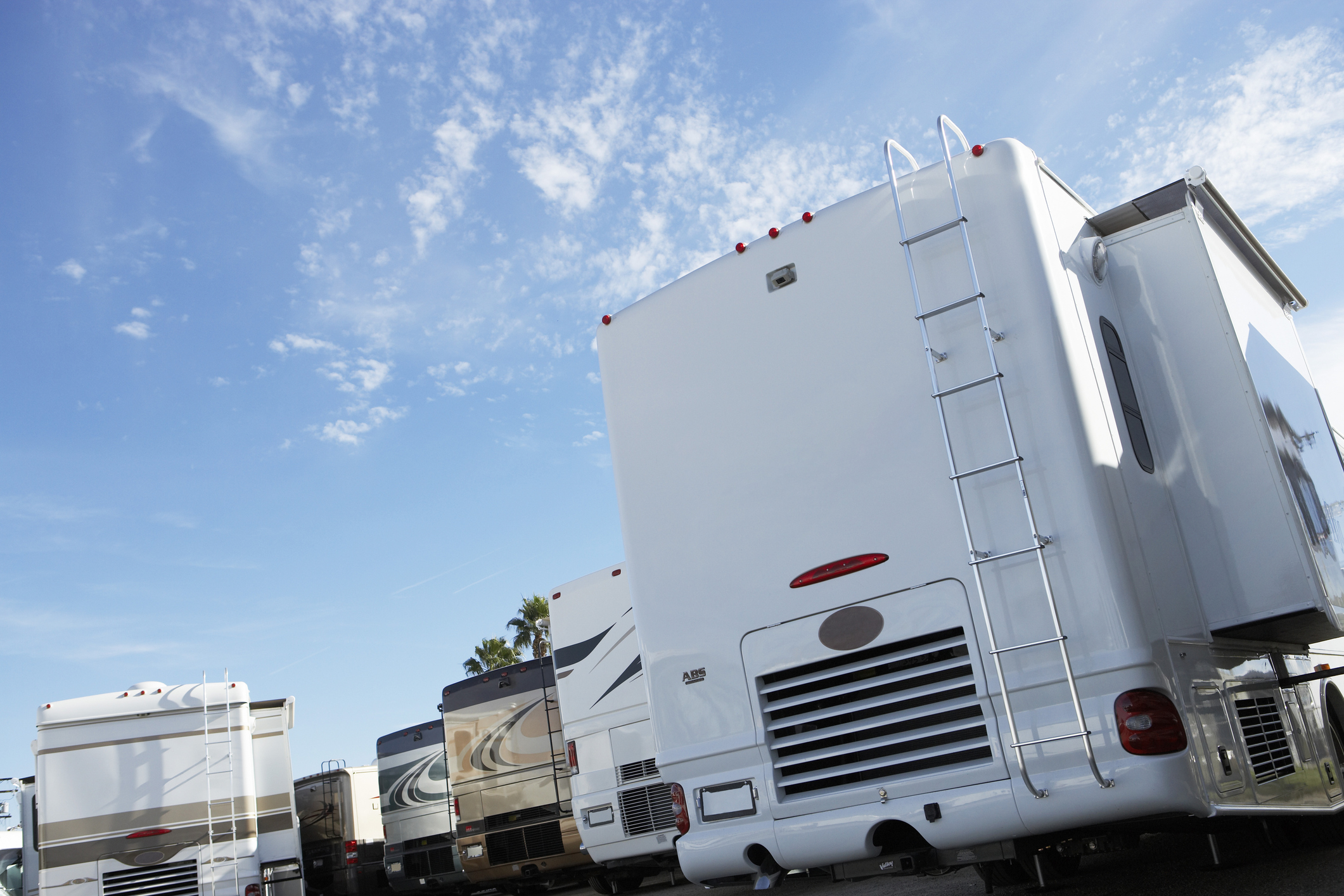 Back of several motorhomes parked in lot, on sunny day