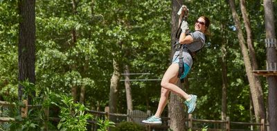 Woman hanging from zip line smiling with trees in background