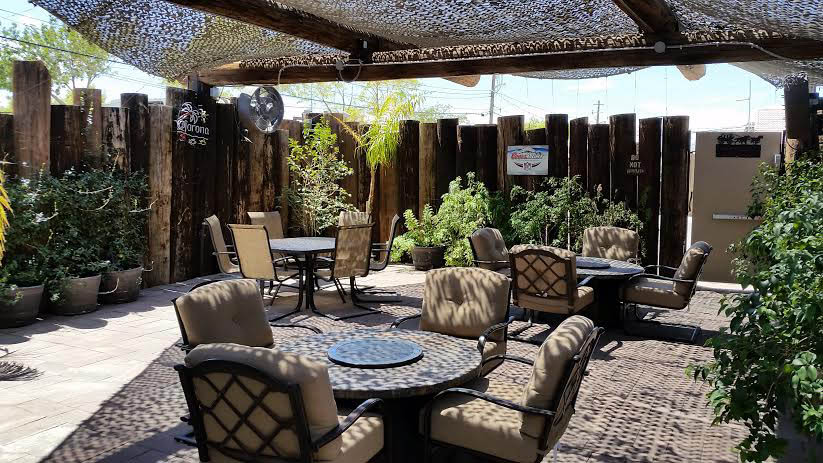 Outdoor patio area of restaurant with three tables and comfortable chairs