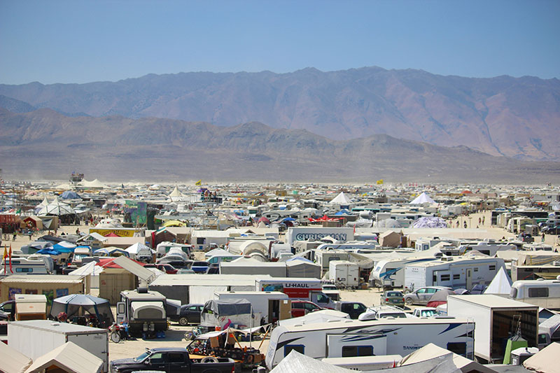 RVs fill the desert landscape as mountains rise in the horizon.