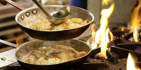 Two sauce pans with potatoes and shrimp cooking over flames