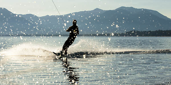 Man gliding across the water on wakeboard