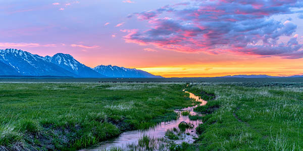 Colorful spring sunset at a green mountain field with a winding stream near Mormon Row historic district in Grand Teton National Park, Wyoming, USA.