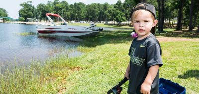 Boy standing with fishing rod with boat in the background