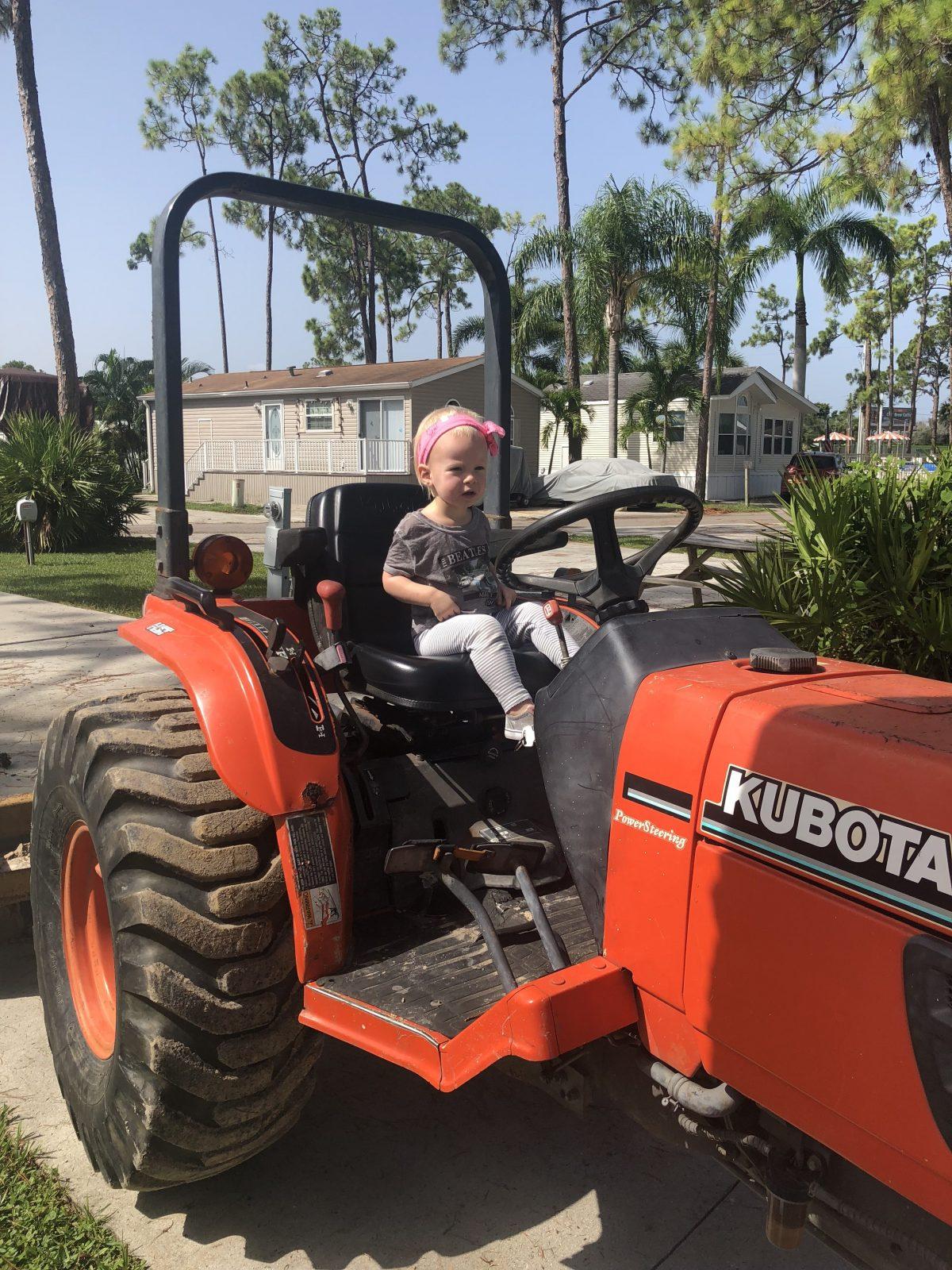 Woodsmoke Camping Resort - girl on tractor