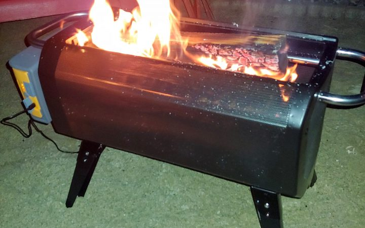 BioLite Firepit with a fire going, placed on the sand