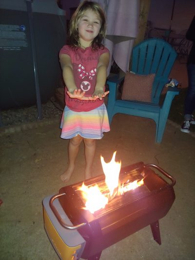 Young girl standing alongside the BioLite Firepit, warming her hands over the fire at the beach.