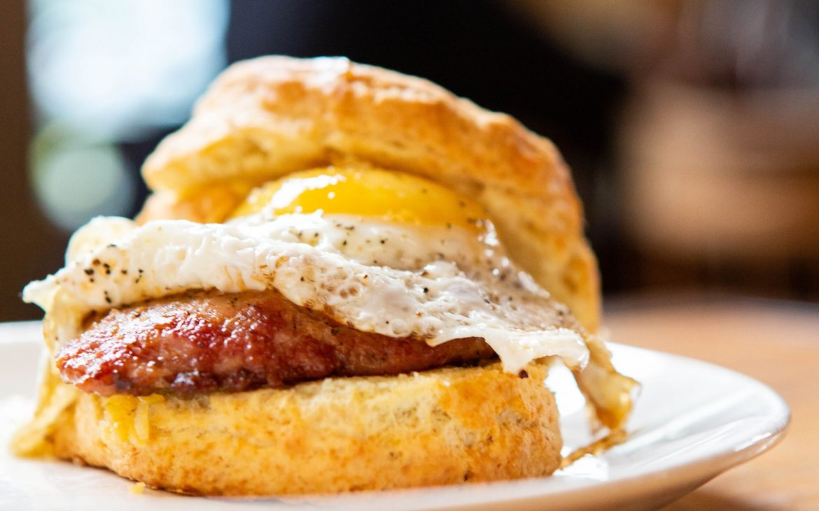 Biscuit with egg and sausage on plate