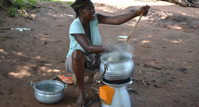 Woman in Uganda using a BioLite home stove to cook.
