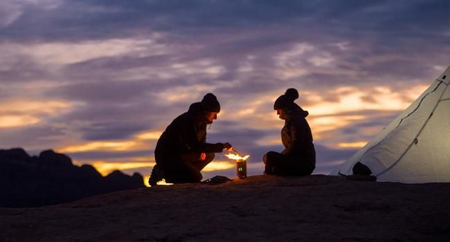 Couple using a BioLite CampStove 2 as the sun is setting behind them.