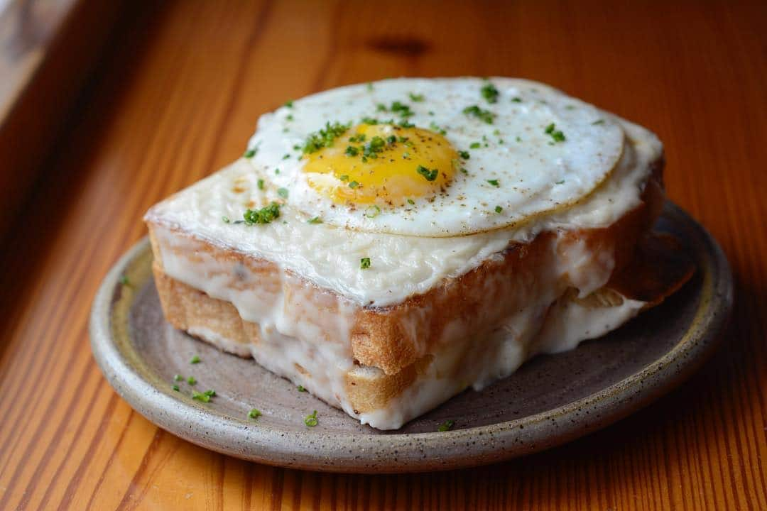 Two thick pieces of toast with melted cheese and eggs