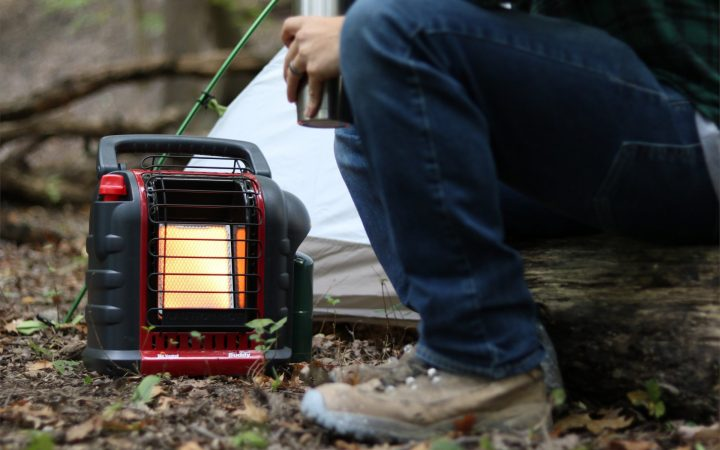 Man sitting on a log in the woods next to a tent and Mr Buddy Heater