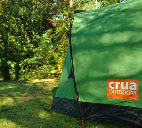Green Crua tent pitched in lush green forested area