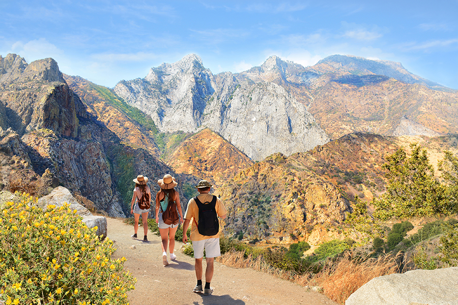 Family with backpacks on hiking trip in the mountains. High mountains view with cloudy sky. Kings Canyon National Park, Fresno, California, USA