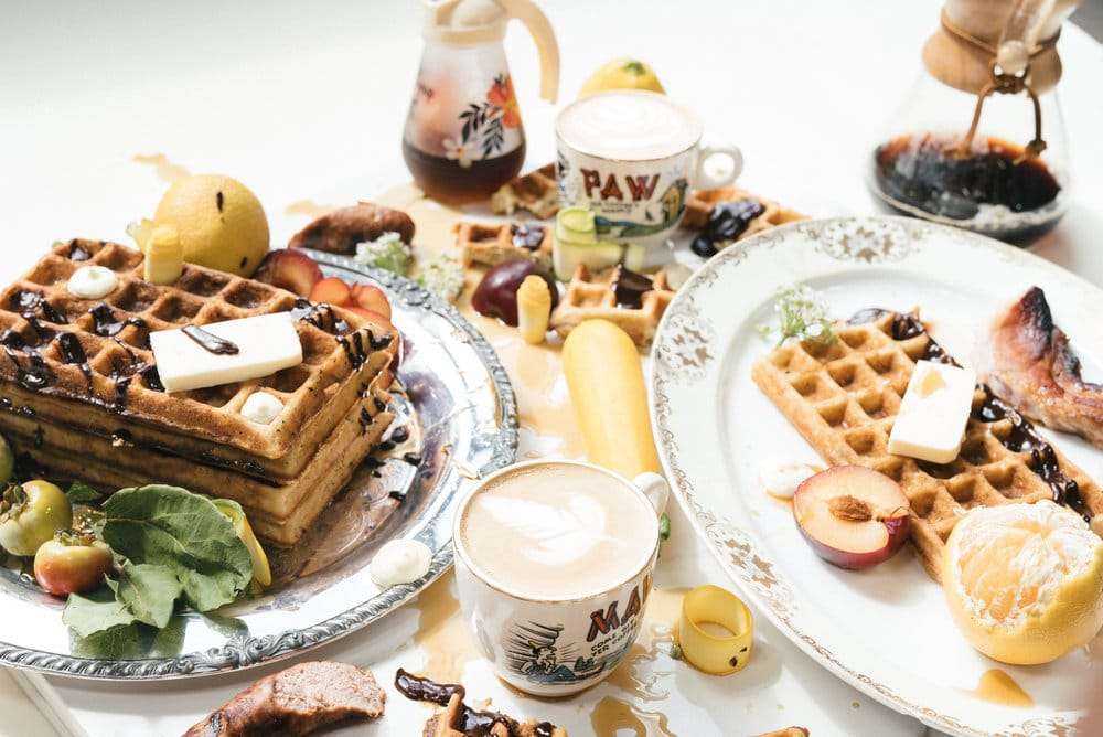 Beautiful breakfast display of waffles, fruit, syrup and coffee on table
