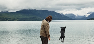 Man looking at dog jumping in lake