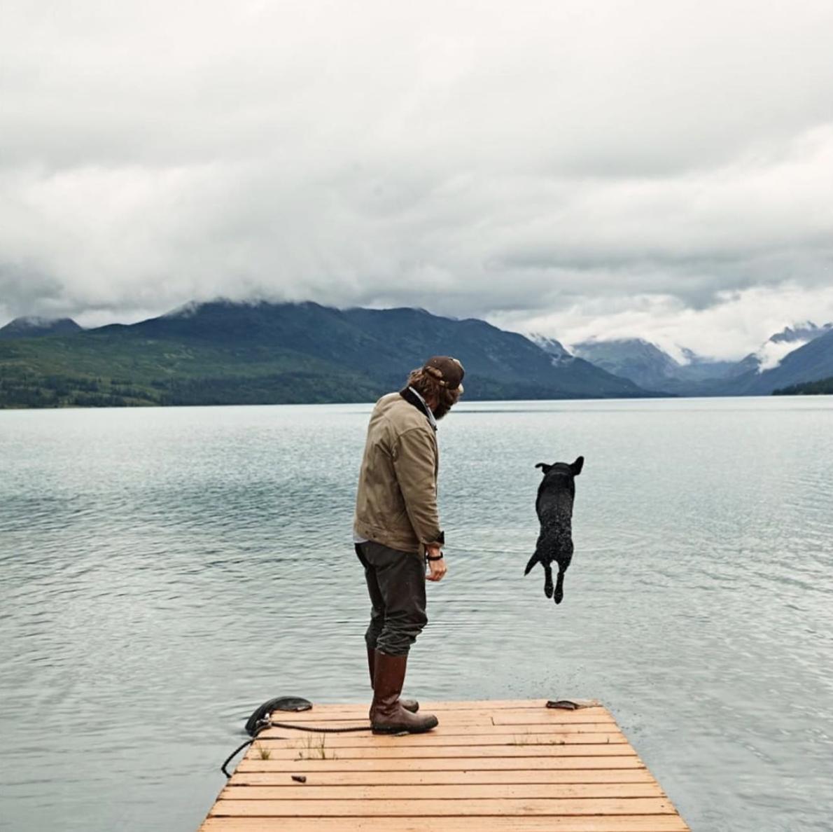 Man looking at dog jumping in lake