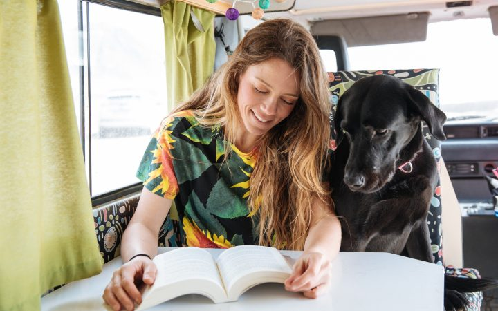 woman and dog reading in camper van