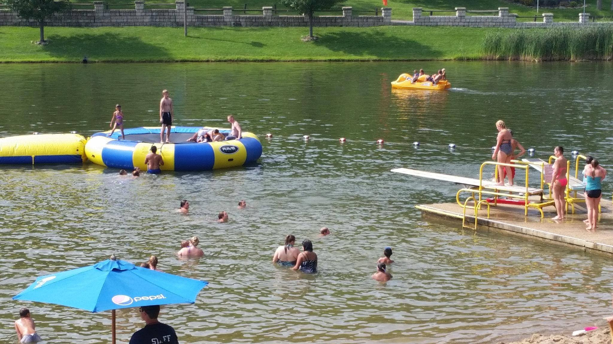 Many people, families, and kids playing in the lake at Wood's Tall Timber Resort