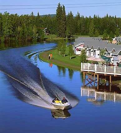Daytime photograph of boat speeding down the Chena River with a house in background