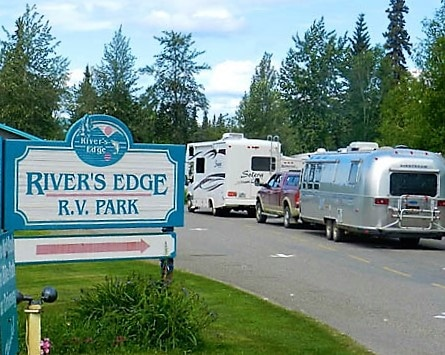 Sign of two RV's driving past the River's Edge RV Park sign with trees in background