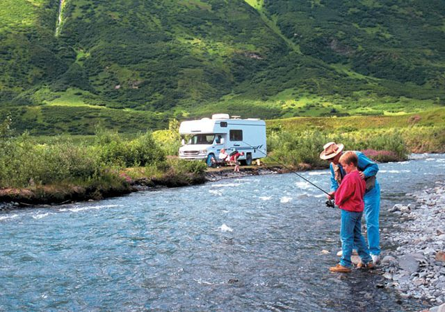 Man fishing with boy on river in alaska