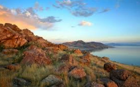 Beautiful red rock and grass hill overlooking the ocean at sunset.