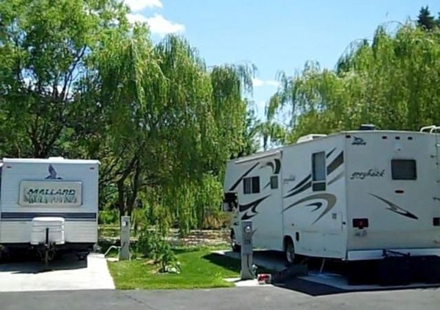 Two RV units in RV spaces, plugged in. Greenery around RVs
