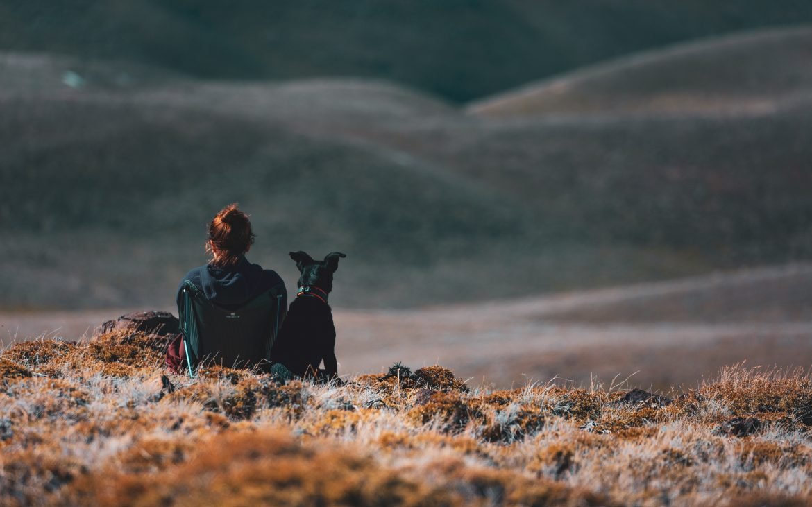 Woman sitting on mountain side with black dog