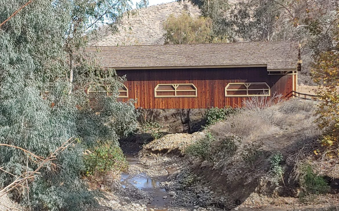 Wooden bridge house over a small creek