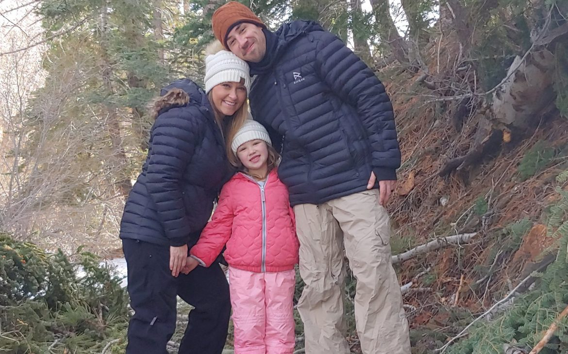 Jeremy P Elder and his family posing near a fallen pine tree in the snow at Angeles Crest National Forest
