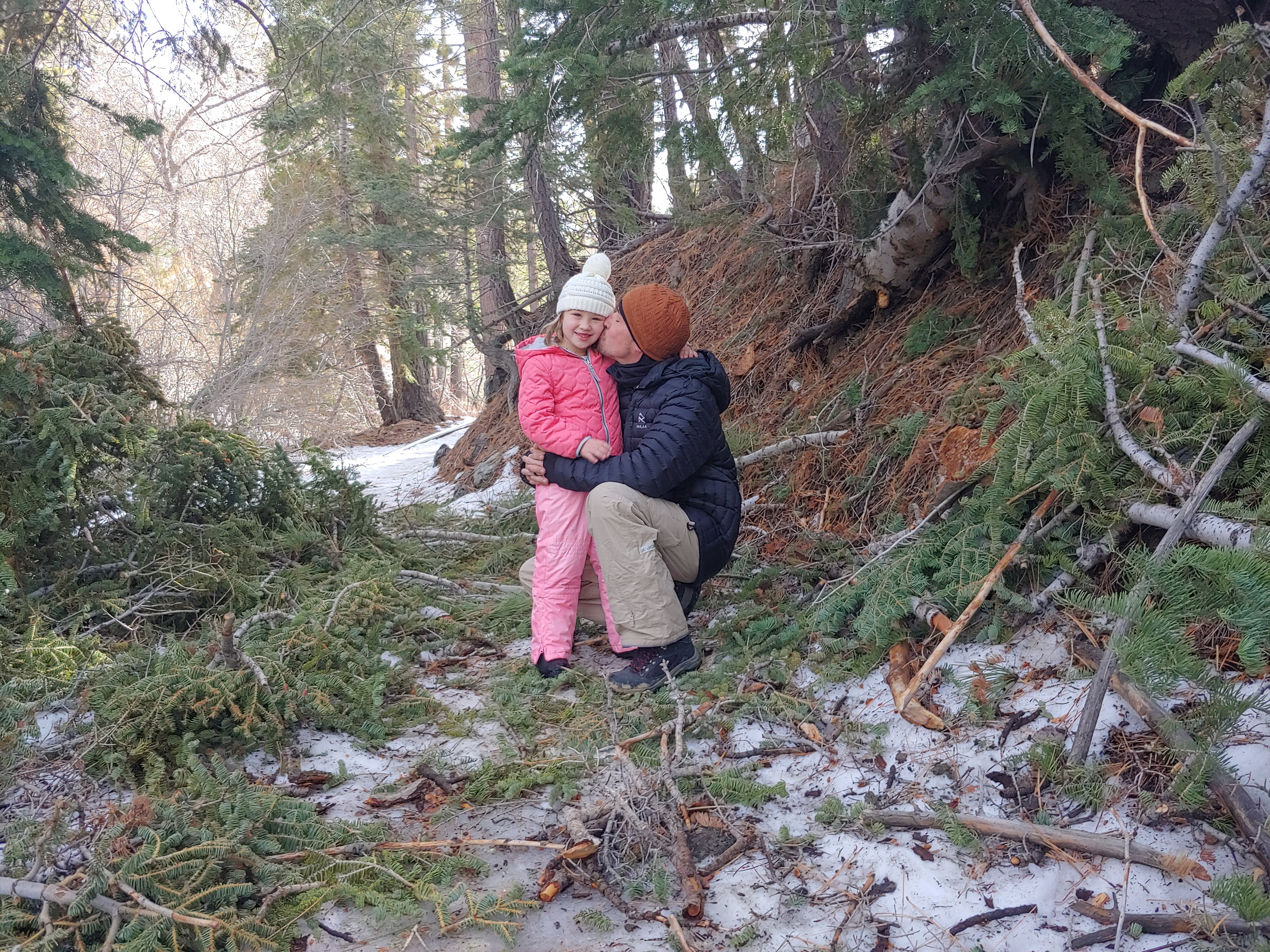 Father kissing daughter in the snow of Angeles Crest
