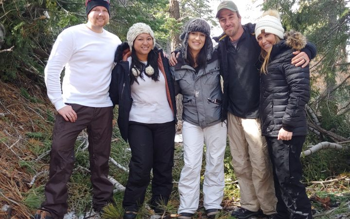 Five adults in snow clothing with snow and pine trees behind them.