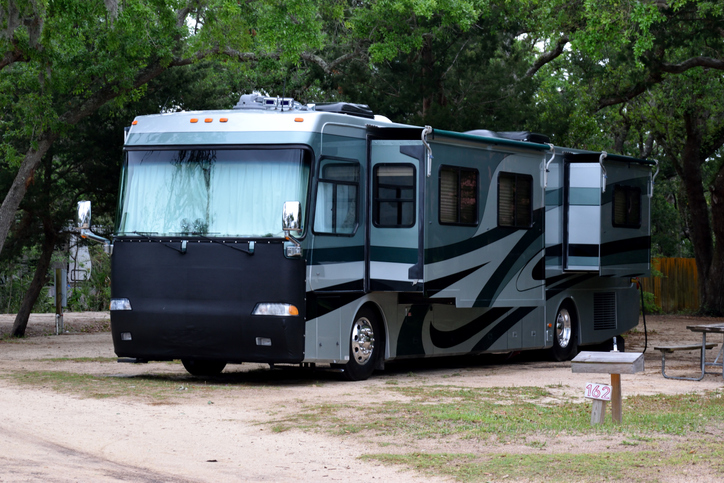 RV with window shades at campsite.