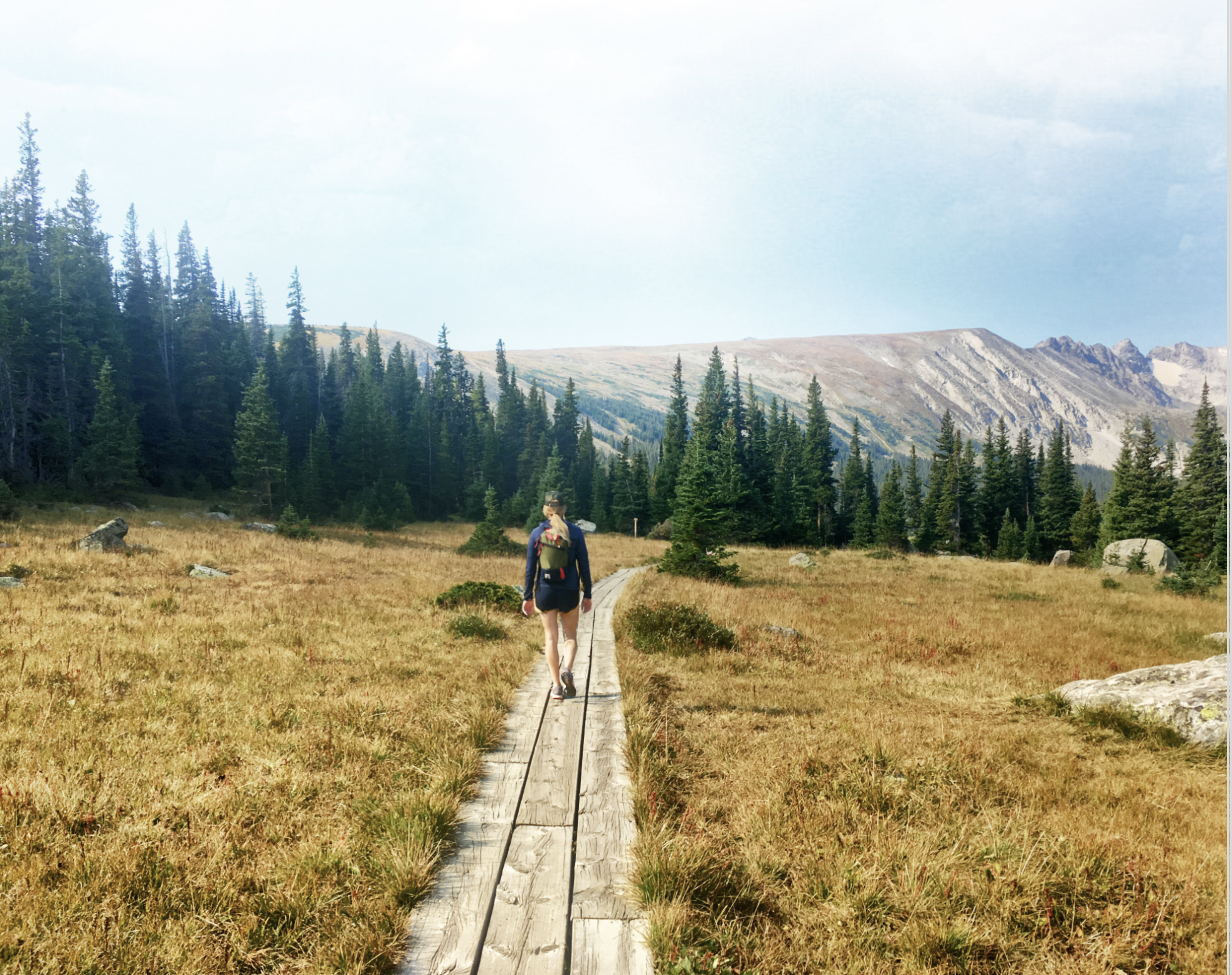 Young Woman walking on a hiking trail through yellowed grass.