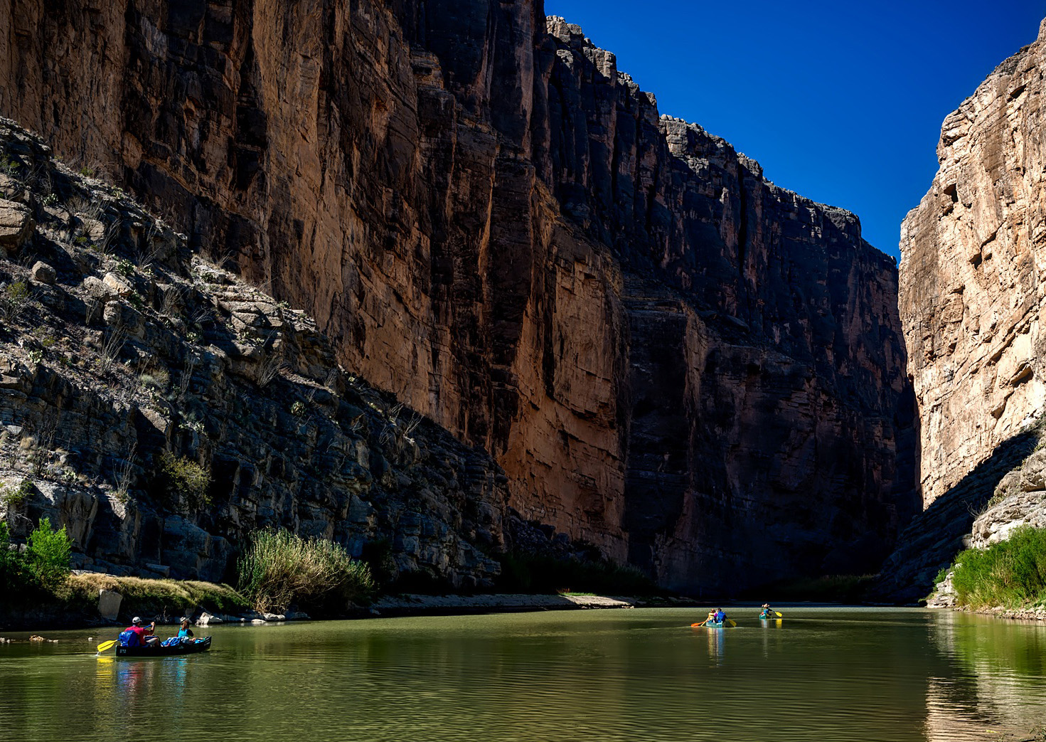 Canoeing in the Rio Grande River under huge cliffs