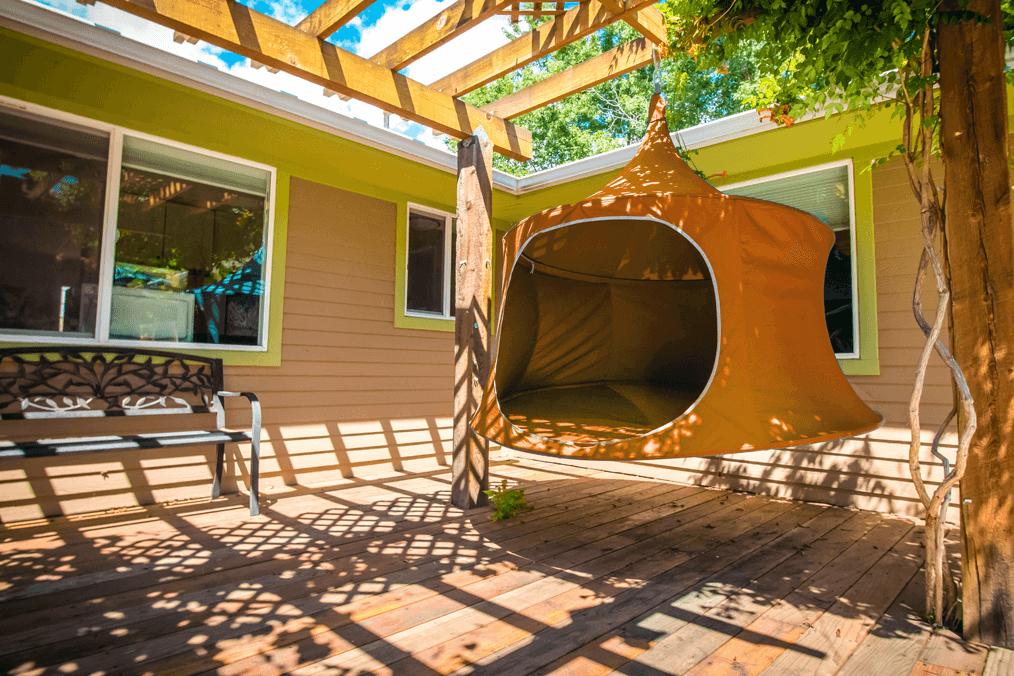 Treepod lounger hanging on patio backyard.