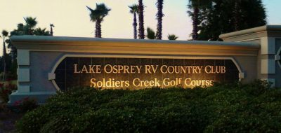 Entry sign to Lake Osprey RV Resort lit at dusk
