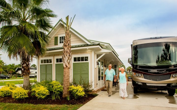 Elderly couple standing between RV and cabin at lake osprey RV resort