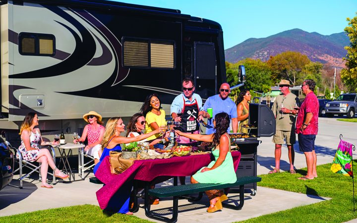 large family and friends enjoying a picnic next to a large RV