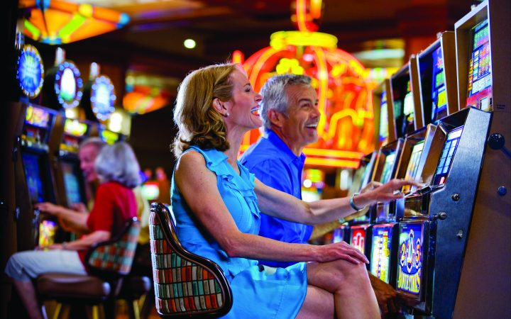Man and woman sitting at slot machine in busy casino