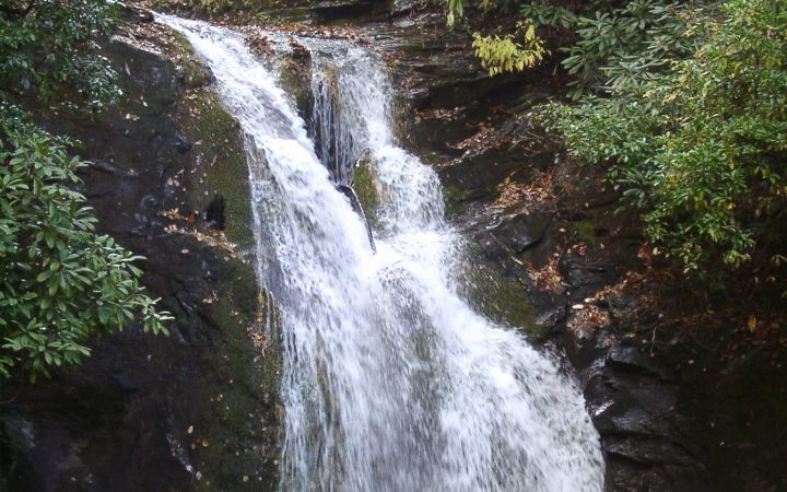 Waterfall falling into lake in wooded area.