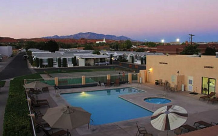 Aerial view of pool at RV resort with beautiful sunset and mountains in background