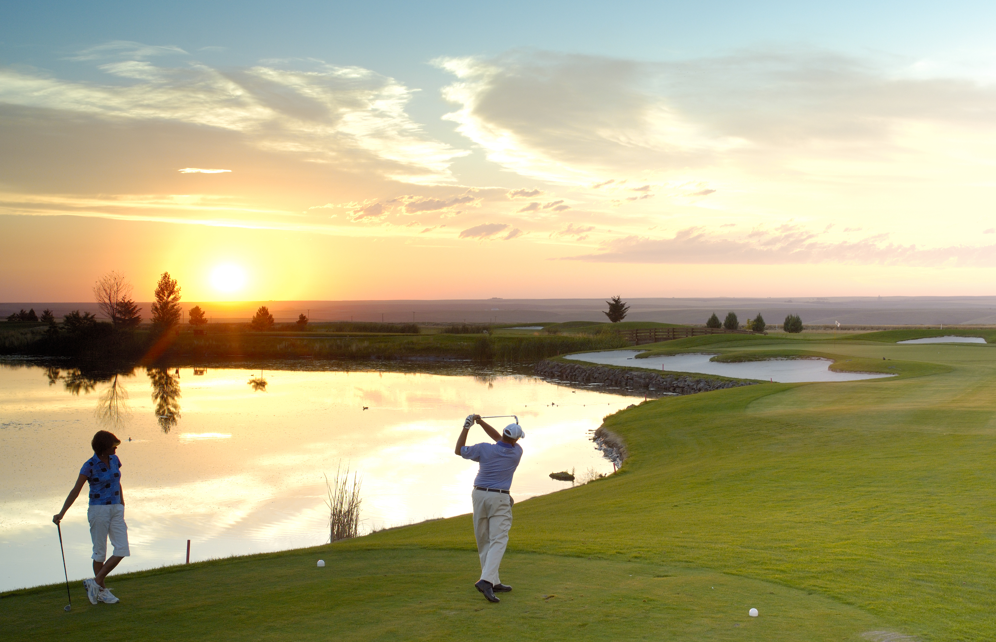Man golfing at sunset on green golf course