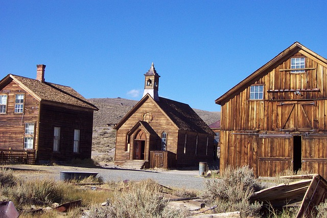 Abandoned ghost town, three wooden buildings, one of them a church.