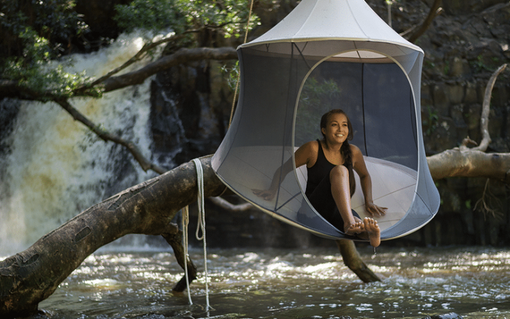 Woman sitting in treepod cabana hanging over a flowing river.