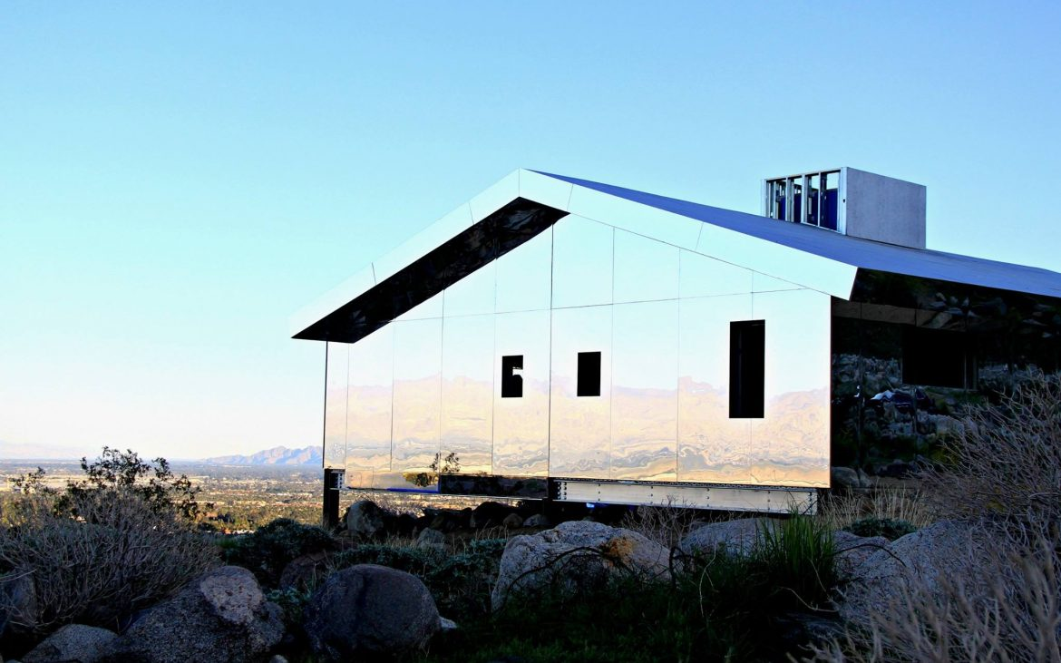 Mirrored covered house in the California desert reflecting land rocks and blue sky