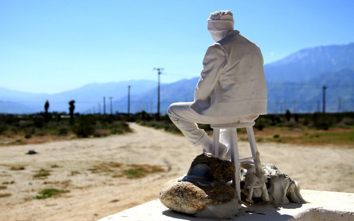 White sculpture of man on stool in the California desert.
