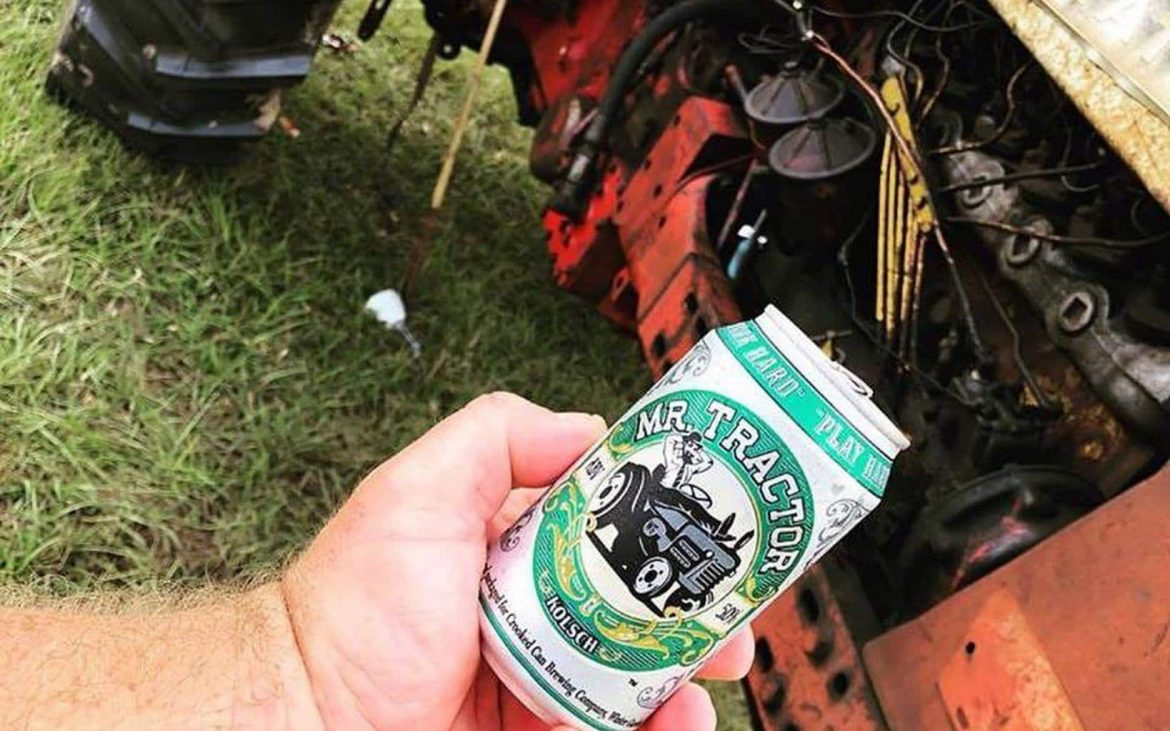 Man holding can beer near tractor