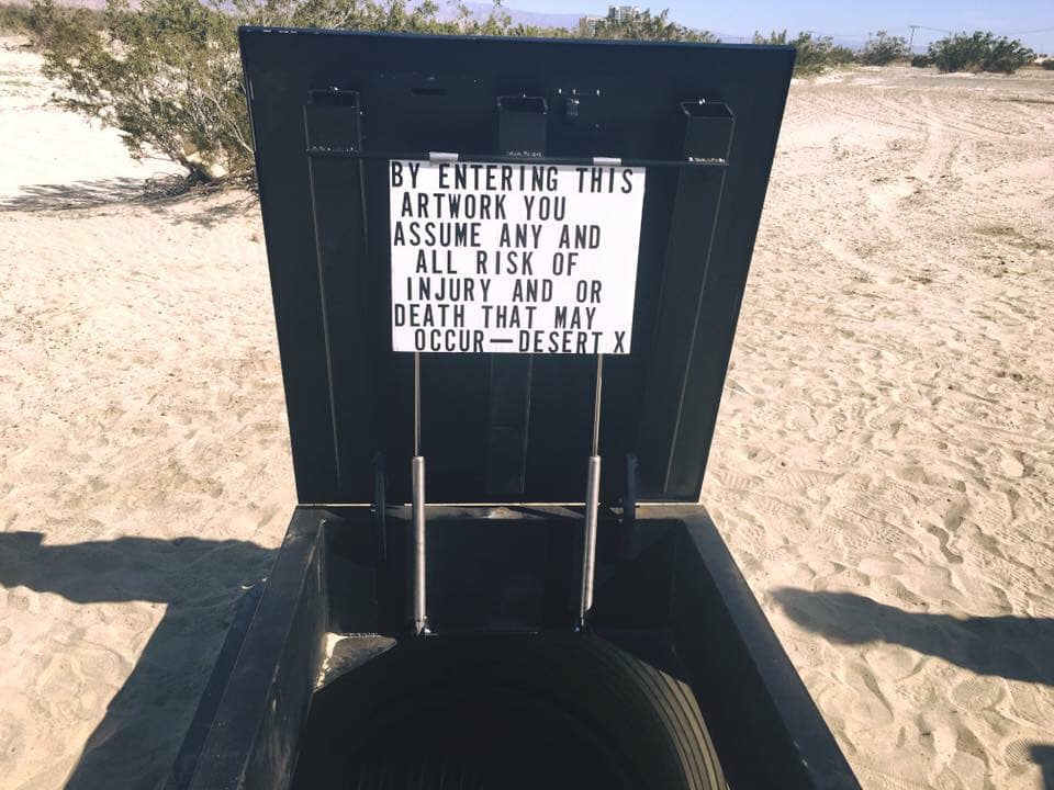 Black bunker in the sand with warning message.